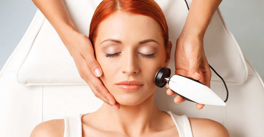 closeup portrait of lovely redheaded woman with closed eyes getting rf-lifting in a beauty salon
